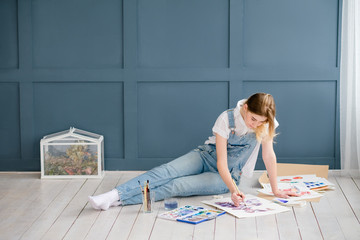 talented artist drawing leisure. creative people lifestyle. relaxed girl painting a picture lying on the floor