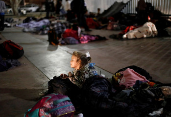 A girl and other members of a caravan of migrants prepare to spend the night near the San Ysidro checkpoint in Tijuana