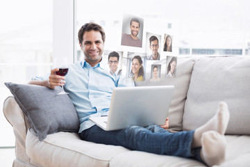 Smiling handsome man relaxing on sofa with glass of red wine using laptop against profile pictures