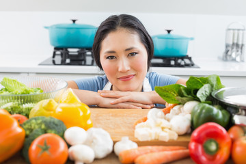 Smiling woman in front of vegetables in kitchen