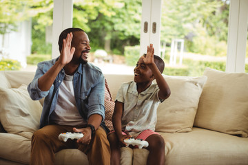 Father and son giving high five to each other while playing video game