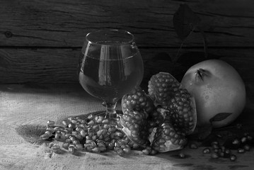 Still Life image of Pomegranate with pomegranate juice and seeds fresh on old wooden plank adjustment color black and whjte