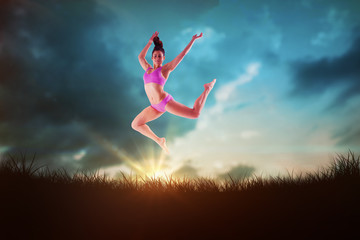 Fit brunette jumping and posing against blue sky over grass
