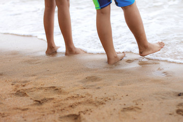 Children are walking on beach.