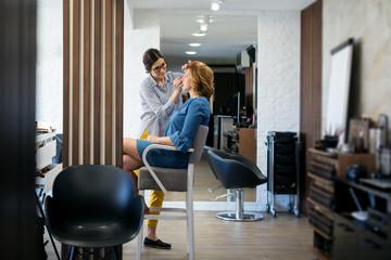 Female make up artist working on model in salon