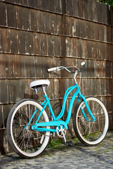 Vintage turquoise bike with white elements standing near the brown wooden wall. Blue bicycle wood