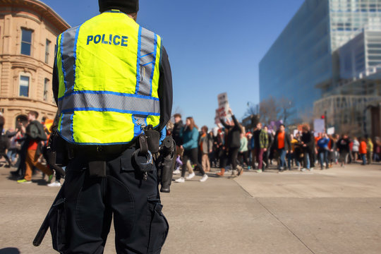 Police standing by to protect teens peacfully marching  in protest of gun violence
