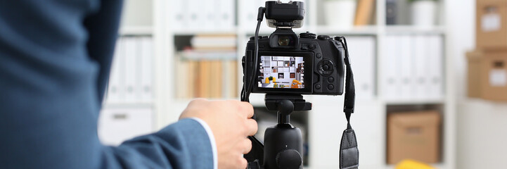 Male arms in suit mount camcorder to tripod