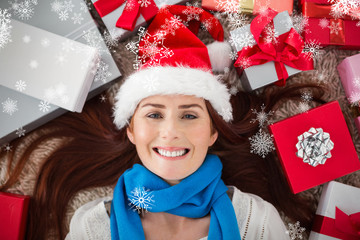 Festive redhead smiling at camera with gifts against snowflakes