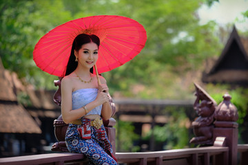 Beautiful Thai girl in traditional dress costume red umbrella as Thai temple where is the public place