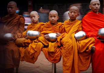 Buddhist monks wait to receive alms during Vesak Day at Boudhanath Stupa in Kathmandu