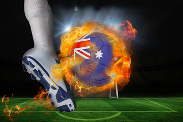 Football player kicking flaming australia flag ball against football pitch and goal under spotlights