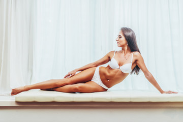 Sexy tanned young brunette female model in underwear sitting posing in white interior with curtains in the background.