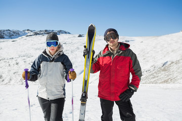 Portrait of a serious couple with ski equipment on snow