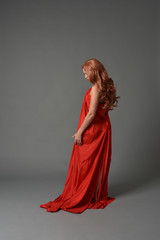 full length portrait of woman wearing red silk gown, on grey studio background.