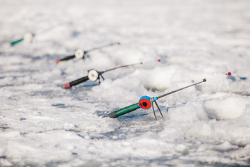 fishman puts the fishing rods on the ice of the river in the winter