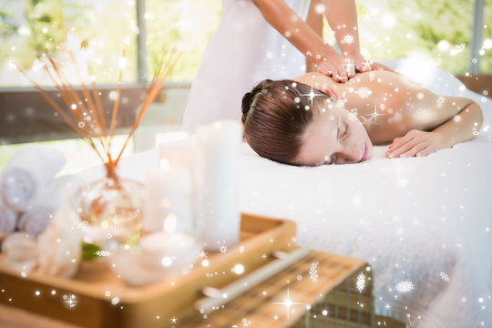 Attractive woman receiving back massage at spa center against snow falling