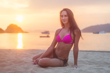 Attractive fit young brunette woman wearing bikini sitting on sea beach at sunset