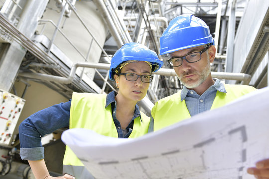 Industrial workers in factory checking blueprint