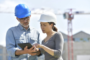 Construction engineers using tablet on building site