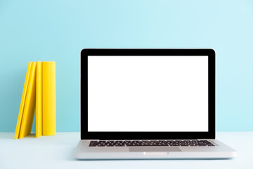 Blank laptop screen of a student or young designer and yellow books. Modern color mock up..
