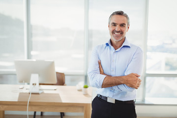 Portrait of smiling executive standing with arms crossed