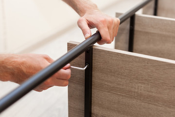 Handyman fastens the shelf to the rack with the help of a hexagon