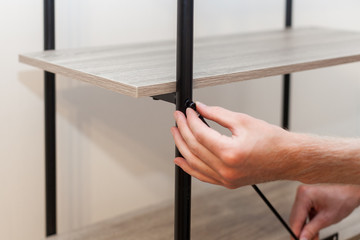 The man folds the bookcase connecting the rails of the shelves