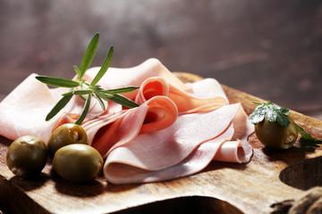 Sliced ham on wooden background. Fresh prosciutto. Pork ham sliced