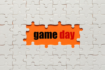 Wall Mural - White details of puzzle on orange background and word Game Day