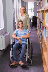 Smiling disabled student with classmate in library