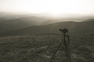 Camera mounted on a tripod, shooting a mountain landscape, toned image