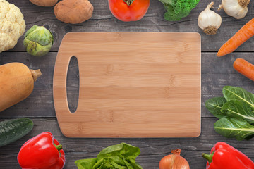 Food cutting board surrounded with vegetables on black wooden desk. Vintage, flat lay, top view.