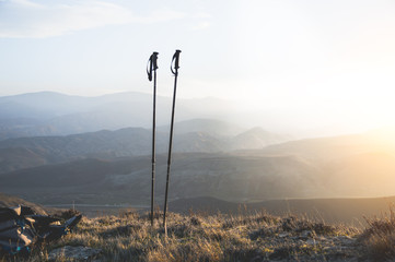 Ascent into the mountains, nordic walking sticks and a backpack, a traveler's set. Wonderful sunset in the background Wall mural