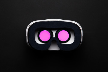 Image of virtual reality glasses with burning pink light on black background