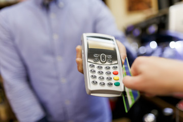 Picture of seller with terminal in hands and buyer with bank card.