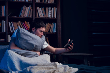 Image of man with insomnia sitting in bed with alarm clock