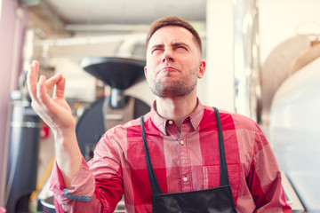 Picture of happy barista in apron on background of industrial coffee grinder