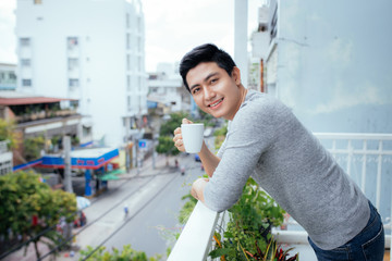 Handsome guy relaxing on a balcony, isolated on a city background