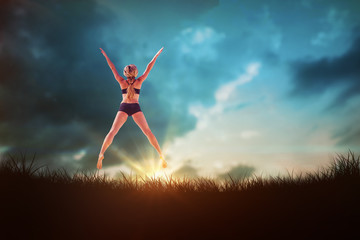 Fit blonde jumping with arms outstretched against blue sky over grass