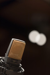 A microphone on a black background with bokeh