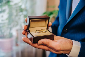 the groom in his hands holds a beautiful box for ornaments and two wedding rings in her