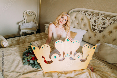 05c2eba3d11 Beautiful blonde bride sitting on bed with big hand made crown in hands