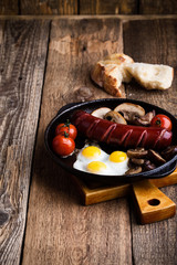 Fried quail eggs, sausage,  tomatoes and mushrooms on cast iron skillet