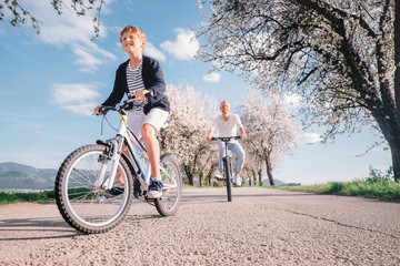 Father and son have a fun active leisure together - ride bicycles on country road
