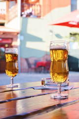 Two glasses of beer standing on a table in a garden pub on a summer sunny day