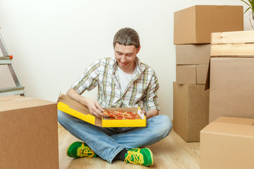Photos of men eating pizza among cardboard boxes