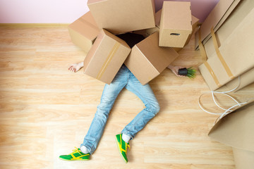 Photo of man in jeans lying under cardboard boxes