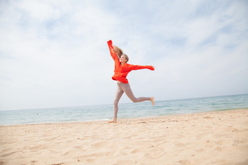 blonde girl jumping on a sandy beach sea shore