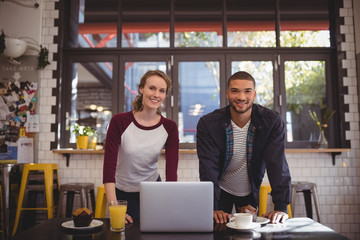 Portrait of smiling young man and woman standing at coffee shop